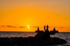 Sillhouette des personnes dans la plage pendant le coucher du soleil Images stock