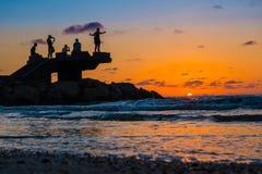 Sillhouette des personnes dans la plage pendant le coucher du soleil Image stock