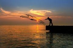 Sillhouette fisherman and sunset on bridge Stock Image