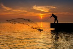 Sillhouette fisherman and sunset on bridge Royalty Free Stock Images