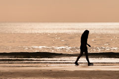 Sillhouette Frau, die auf dem Strand waliking ist Stockfoto