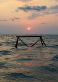 Sillhouette of hammock in sea on sunset Royalty Free Stock Photography