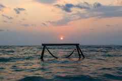 Sillhouette of hammock in sea on sunset Stock Photo