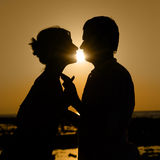 Sillhouette of kissing couple at sunset. Silhouette of kissing couple over orange sunset background Royalty Free Stock Photos