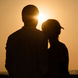 Sillhouette of loving couple at sunset. Silhouette of loving couple over orange sunset background Stock Photo