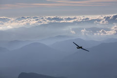 Sillhouette of small plane over clouds and mountains.  Royalty Free Stock Photography