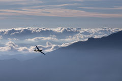 Sillhouette of small plane over clouds and mountains Royalty Free Stock Photo