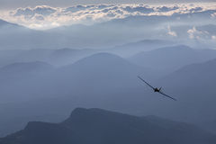 Sillhouette of small plane over clouds and mountains Royalty Free Stock Photos
