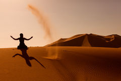 Sillhouette of woman playing and throwing with sands in Desert S Stock Image