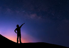 Sillhouette of woman standing next to the milky way. And pointing on a bright star Stock Photo