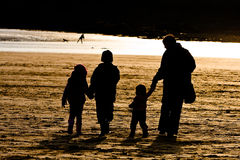 Sillhouetted Family on Beach Stock Photo