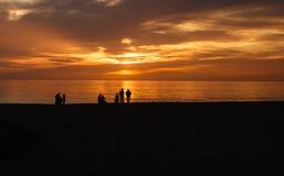 Sillhouettes des personnes sur la plage au coucher du soleil Images stock