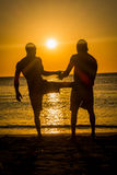 Sillhouettes of two men in the beach during sunset Stock Image