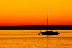 Sillhoutte della barca ad alba Immagine Stock