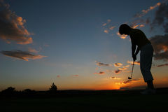 Sillhoutte of lady golfer. Weird sunset Silhouette of lady golfer Stock Image