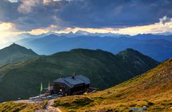 Sillian hut in Carnic Alps main ridge and Hohe Tauern at sunset. Sillian hut in Carnic Alps main ridge with Helm / Elmo and Hochgall / Collalto peaks, blue Stock Photography