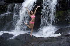 Silliness at the Waterfall. Lovely young Hispanic African American woman being silly at a waterfall royalty free stock image