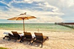 Sillones de la playa debajo del paraguas en la orilla Foto de archivo libre de regalías