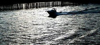 Sillouette της βάρκας μετά από τις συσσωρεύσεις στοκ εικόνες