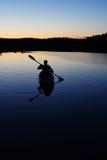 Sillouette dell'uomo che kayaking sul lago Fotografie Stock