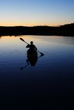 Sillouette of man kayaking on lake Stock Photos