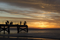Sillouettedmensen die - Normanville-Pier bij Zonsondergang vissen Stock Afbeelding