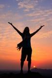 Sillouettedvrouw met haar wapens omhoog bij zonsondergang bovenop de heuvel, stock fotografie