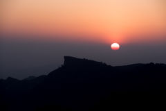Silluate Photo of Sunset behind the mountains peak Royalty Free Stock Photography