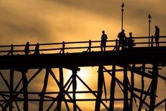 Silluatemens op houten brug tijdens bij zonsondergang Royalty-vrije Stock Afbeelding