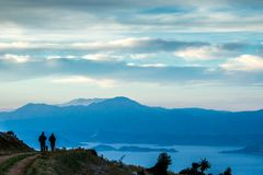 Free Silluettes Of Two Men And A Dog Enjoying The Great View From Mountain Stock Image - 115411041