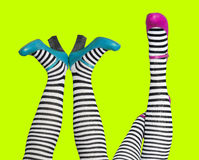 Silly. Two pairs of legs, stripy stockings and bright shoes Stock Images