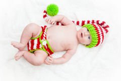 Silly Baby in Striped Knit Hat. Baby wearing red white and green striped knit hat lying on his back looking festive for the holidays Stock Photos