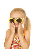 Silly blond girl smiling putting on her sunglasses Stock Photography