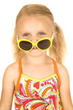 Silly blond girl wearing swimsuit and sunglasses down on nose Royalty Free Stock Images