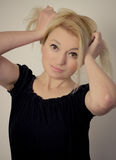 Silly. Blond woman being silly and holding her hair royalty free stock photography