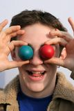 Silly boy. S holding in front of his eyes easter eggs Stock Image