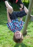Silly boy plays on outside swing set Royalty Free Stock Image