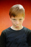 Silly boy. Silly  boy  pullimg faces  in front of a red background Royalty Free Stock Photography
