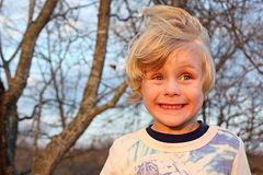 Silly Boy Smiling Outside. A cute toddler boy smiles really big and silly and looks away as the sun is setting Royalty Free Stock Photography