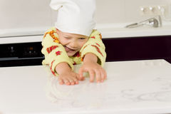 Silly boy wearing toque playing with flour Royalty Free Stock Photos