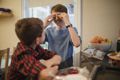 Silly Brussel Sprout Eyes. Two brothers are helping with making a christmas dinner. The eldest boy is looking at his younger brother with brussel sprouts held up stock image