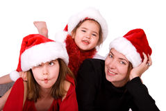 Silly Christmas portrait. Christmas portrait of a mother with her two daughters, all of them are wearing Santa hats. Girl on left is pulling a silly face and Royalty Free Stock Images