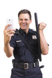 Silly cop taking selfie with baton Stock Photography
