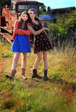 Silly Country Girls. Two silly teenage country girls wearing boots and dresses, hanging out in front of a rusty old truck. Shallow depth of field Royalty Free Stock Images