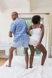 Silly couple dancing on bed together Royalty Free Stock Photography