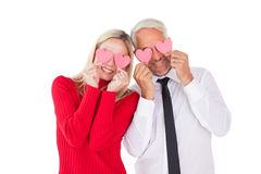 Silly couple holding hearts over their eyes Stock Photo