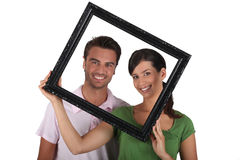 Silly couple with picture frame Royalty Free Stock Photo