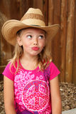 Silly cowgirl in a straw hat. Expression of a silly little blond farm girl with big eyes in pink shirt and a western straw cowboy hat. Shallow depth of field Stock Image