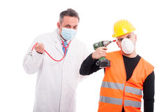 Silly doctor and constructor playing with their tools. Stethoscope and drill isolated on white background Stock Photography