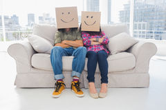 Silly employees with arms folded wearing boxes on their heads. With smiley faces on a couch stock photography